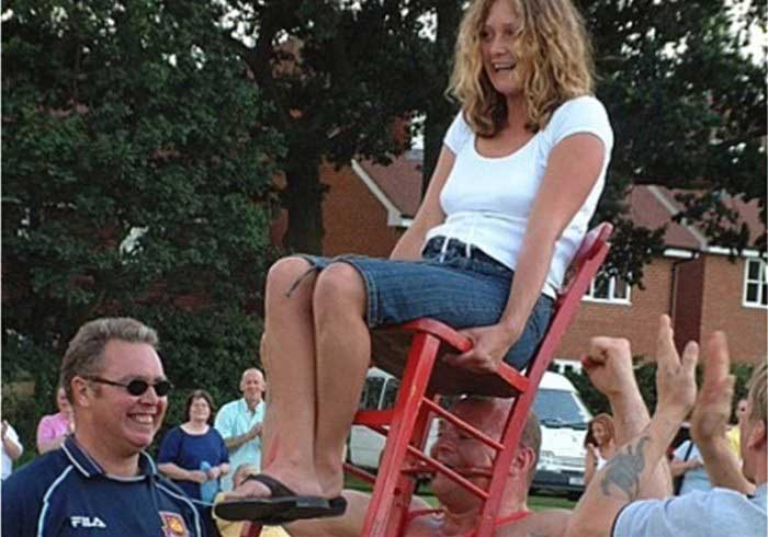Strongman Holding Lady on a Chair