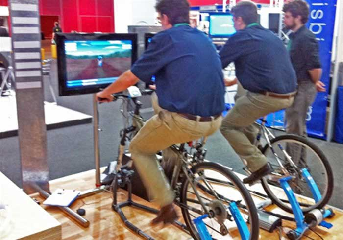 Men riding bicycle simulators at an exhibition