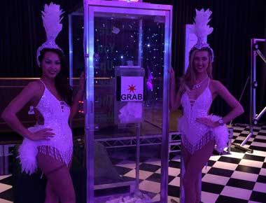 Showgirls standing by a cash cube